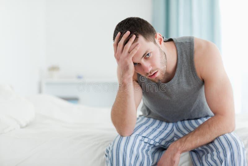 Zmęczony mężczyzna obsiadanie na jego łóżku zdjęcie royalty free