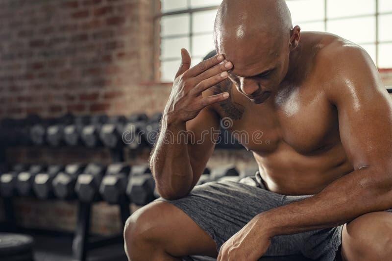 Zmęczony mężczyzna odpoczywa po silnego treningu zdjęcia royalty free