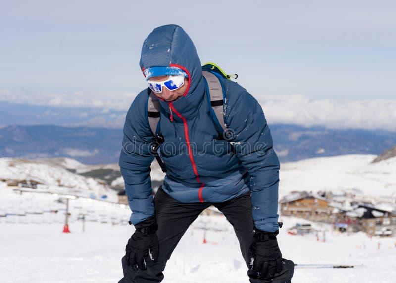 Zmęczony mężczyzna wyczerpujący po szczytowego szczytu trekking osiągnięcia w śnieżnym halnym zima krajobrazie zdjęcia royalty free