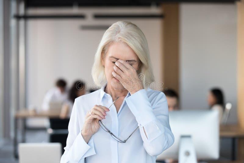 Zmęczony męczący starszy żeński pracownik zdejmuje szkła czuje eyestrain zdjęcia stock