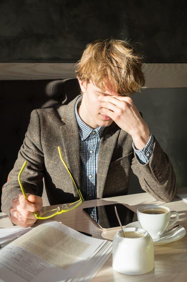 Zmęczony męski uczeń bierze daleko czytać eyeglasses i naciera jego oczy podczas kawowej przerwy przy restauracją obrazy stock