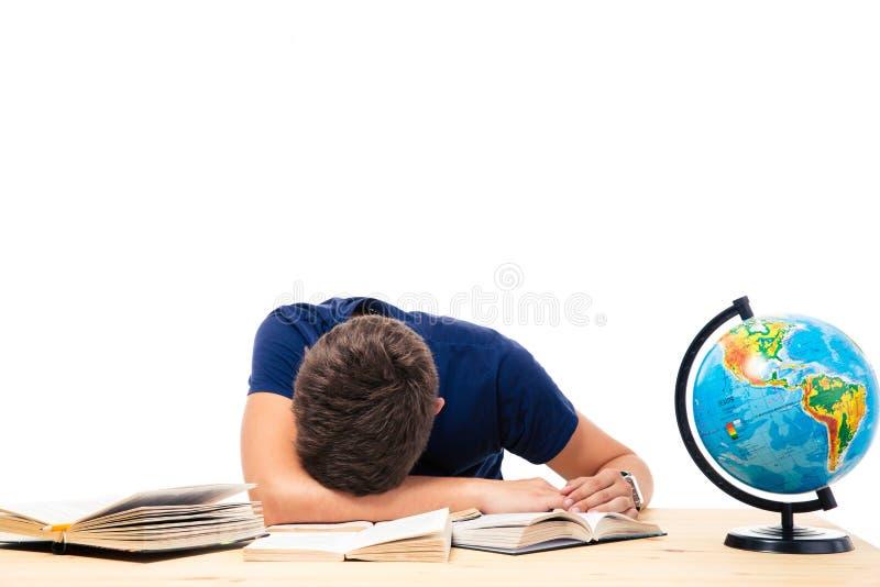 Zmęczony męskiego ucznia dosypianie na stole zdjęcie stock