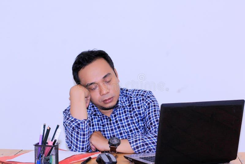 Zmęczony młody azjatykci atrakcyjny mężczyzna śpi przy miejsce pracy obraz royalty free