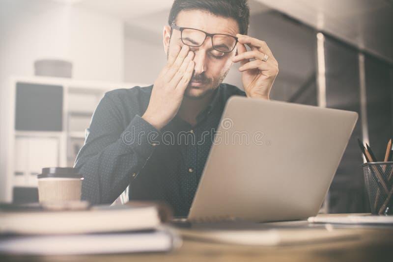 Zmęczony młody biznesowy mężczyzna w biurze zdjęcia royalty free