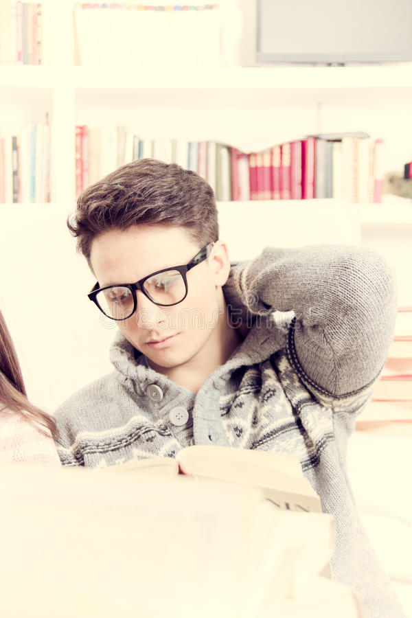 Zmęczony młody człowiek czyta książkę z szkłami zdjęcie royalty free