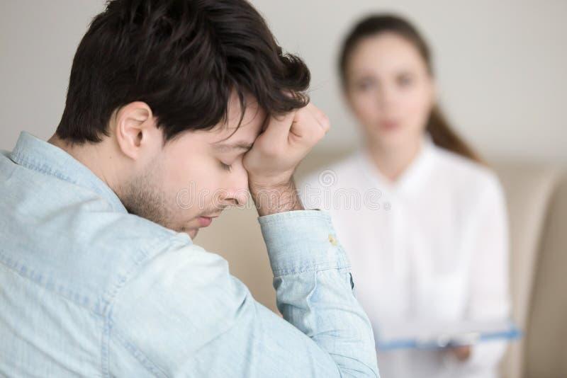 Zmęczony młody człowiek ma migrenę podczas gdy pracujący lekarkę lub odwiedzający fotografia stock