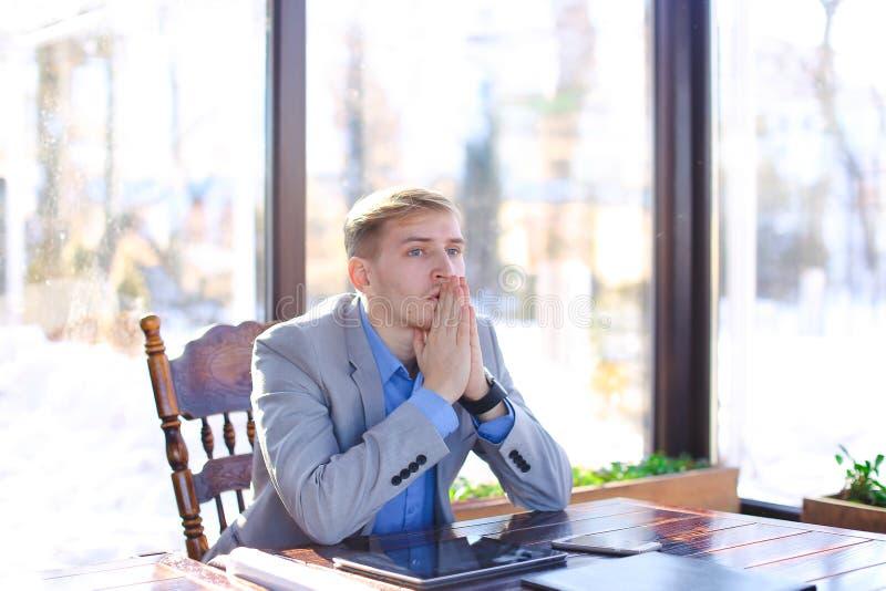 Zmęczony młody profesora obsiadanie przy kawiarnią z rolka papierem, smartphon zdjęcia royalty free