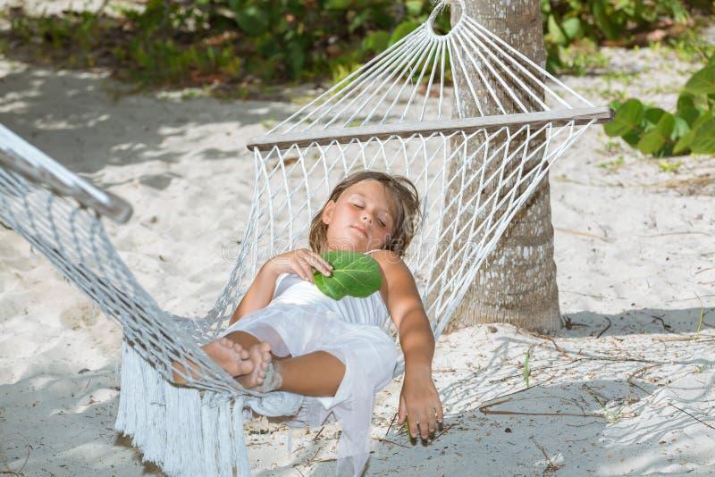 zmęczony małej dziewczynki lying on the beach, dosypianie na hamaku w ogródzie i fotografia royalty free