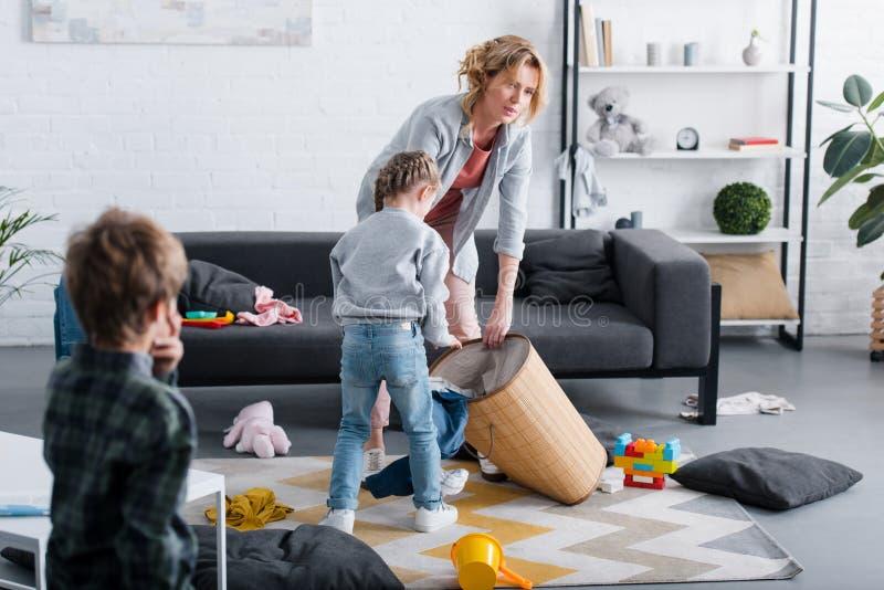 zmęczony macierzysty kładzenie bawi się w koszu podczas gdy niegrzeczny dzieci bawić się ilustracja wektor