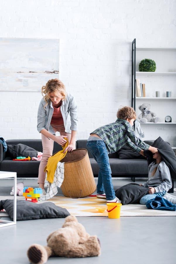 zmęczony macierzysty kładzenie bawi się w koszu podczas gdy niegrzeczny dzieciaków walczyć ilustracja wektor