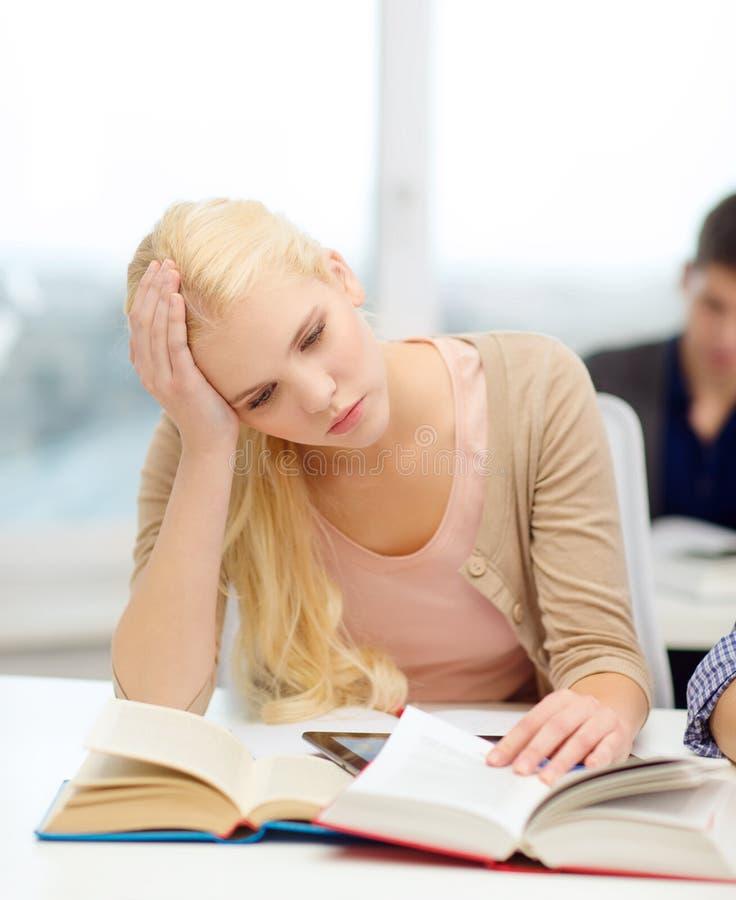 Zmęczony nastoletni uczeń z pastylek książkami i komputerem osobistym zdjęcia royalty free