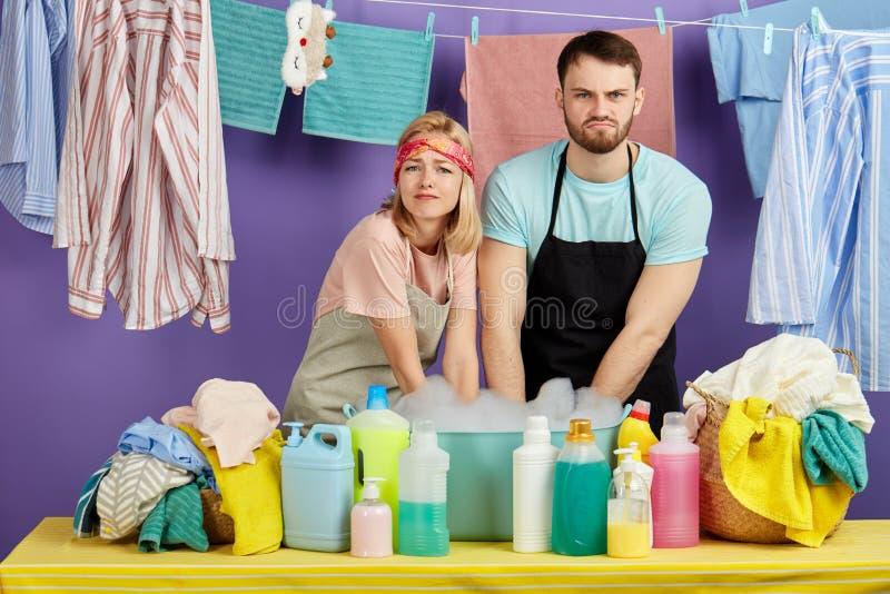 Zmęczony nieszczęśliwy smutny mężczyzna i kobieta nienawidzimy robić pralni obraz stock