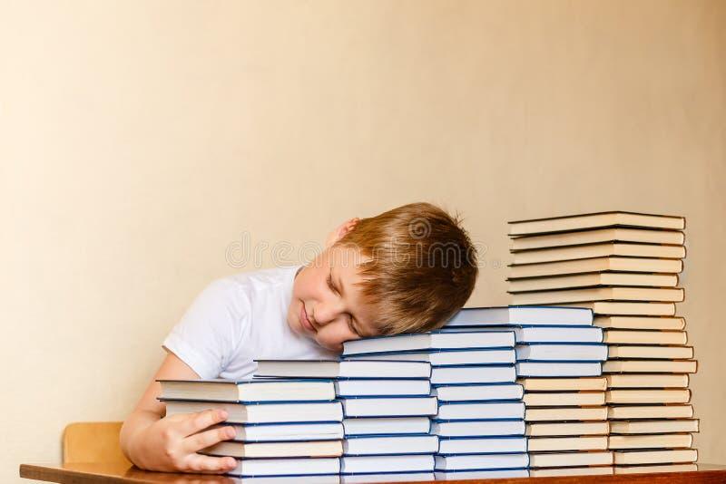 Zmęczony ośmioletni chłopiec dosypianie na książkach przy stołem dzieci i czytanie obrazy royalty free