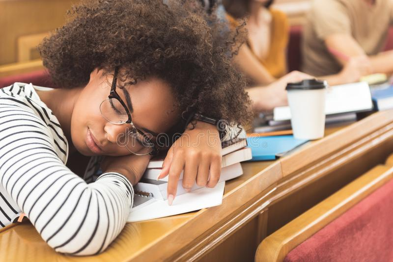 Zmęczony oliwkowy dziewczyny drzemanie na wykładzie zdjęcie royalty free