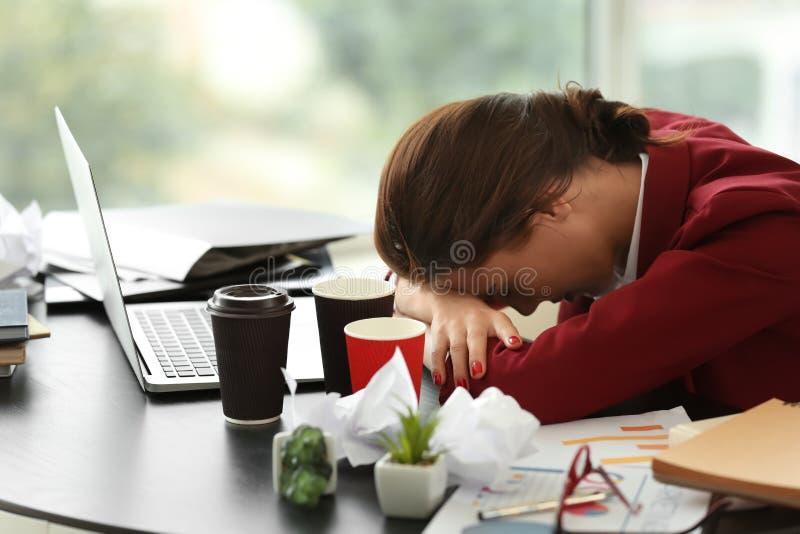 Zmęczony pracownik z mnóstwo pracy obsiadaniem przy stołem w biurze fotografia stock