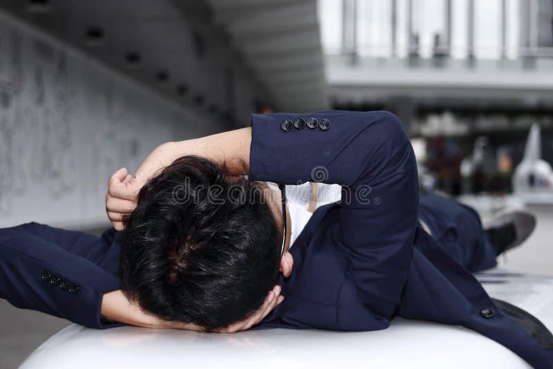 Zmęczony przygnębiony młody Azjatycki biznesowego mężczyzna łgarski puszek i uczucie stresujący obrazy royalty free