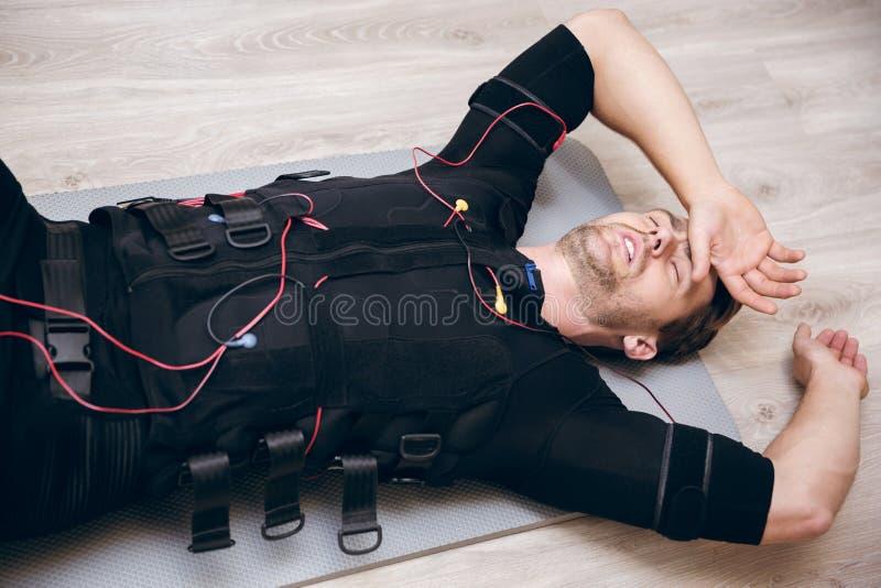 Zmęczony sportowa lying on the beach na podłoga po trenować z ems obraz royalty free