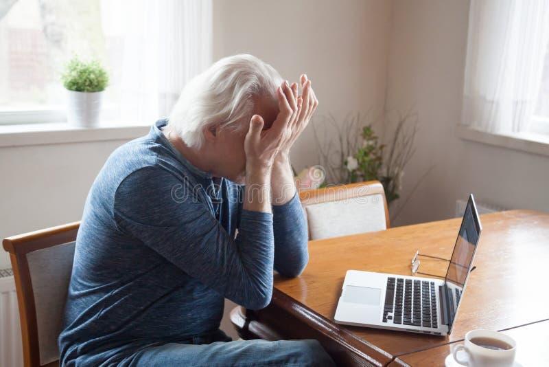 Zmęczony starszego mężczyzny cierpienie od migreny masowania ono przygląda się fotografia stock