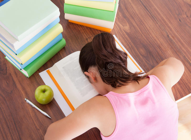 Zmęczony studencki dosypianie na książce fotografia stock