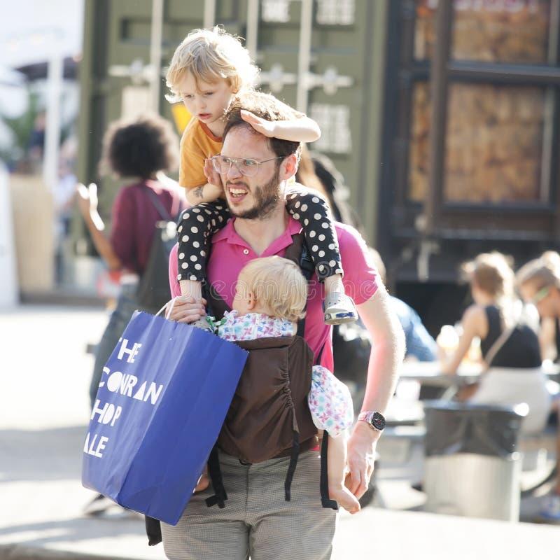 Zmęczony tata z dwa dziećmi iść dla robić zakupy Stary dziecko siedzi fotografia royalty free