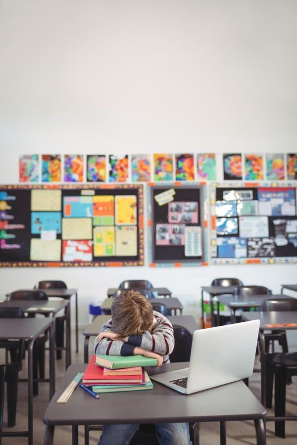 Zmęczony uczniowski dosypianie na stercie książkowy obsiadanie w sala lekcyjnej obraz royalty free