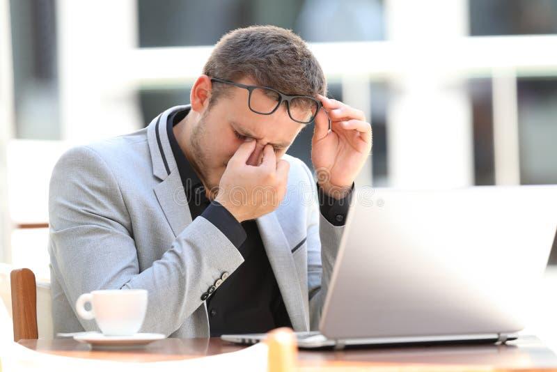 Zmęczony wykonawczy cierpienia eyestrain w sklep z kawą fotografia stock
