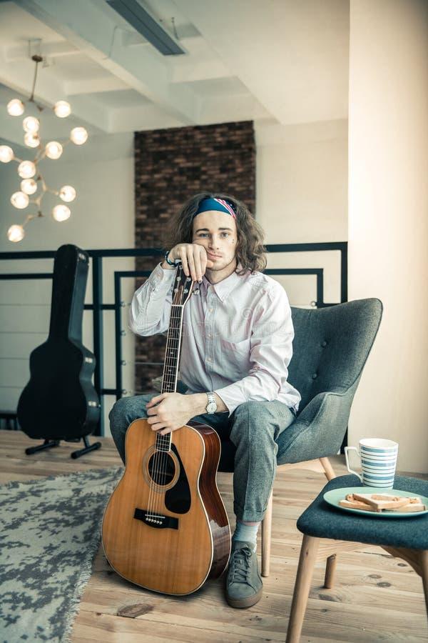 Zmęczony wzburzony facet z kolorowymi bandanami opiera na jego gitarze zdjęcie stock