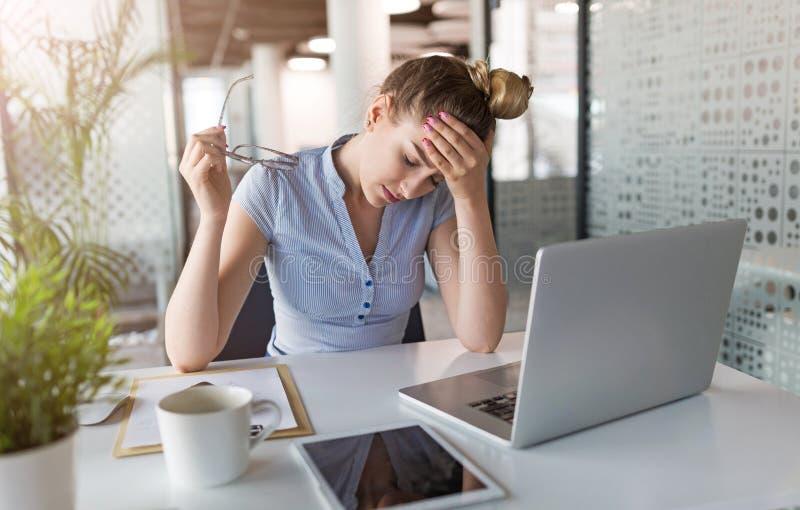 Zmęczony, zaakcentowany bizneswoman przy laptopem w biurze, obraz royalty free