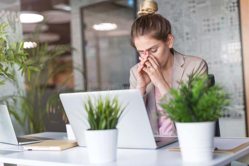Zmęczony, zaakcentowany bizneswoman przy laptopem w biurze, zdjęcia royalty free