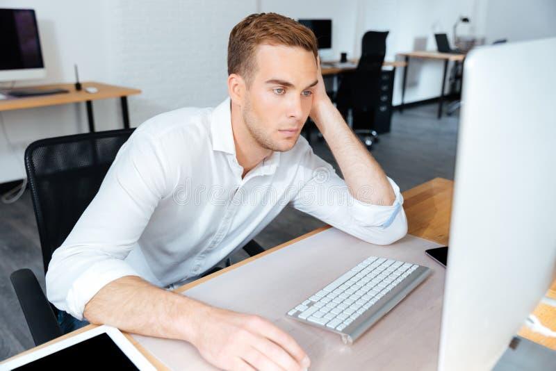 Zmęczony zanudzający młody biznesmen pracuje z komputerem w biurze zdjęcia royalty free