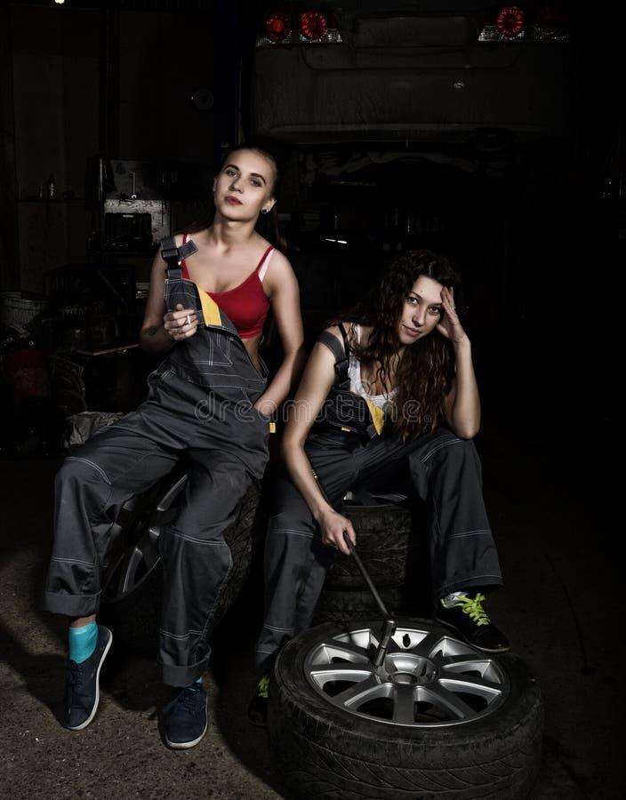 Zmęczonych mechaników seksowne dziewczyny siedzi na stosie opony na samochodu naprawach i dymu, jeden dziewczyny trzyma wyrwanie  zdjęcia royalty free