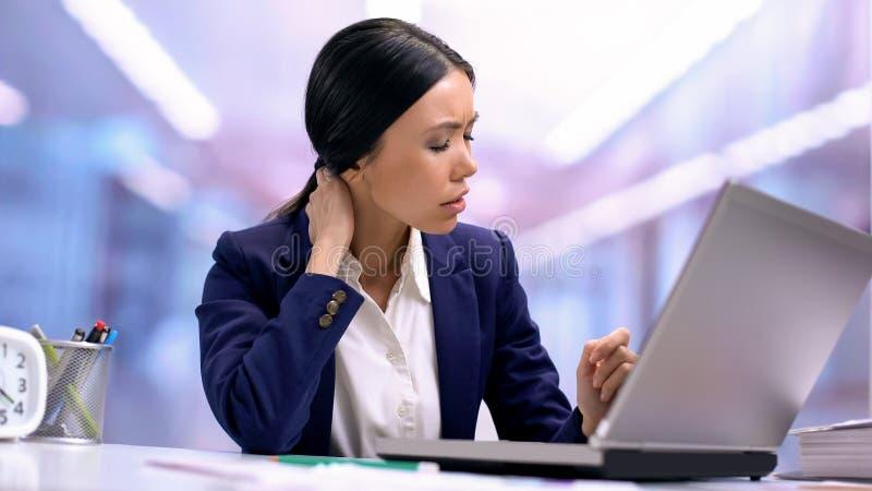 Zm?czony biznesowej kobiety cierpienie od szyja b?lu obsiadania przodu laptopu, opieka zdrowotna zdjęcia royalty free