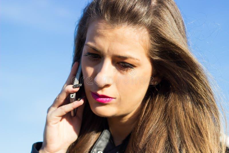 Zmartwiona dziewczyna opowiada na telefonie fotografia stock