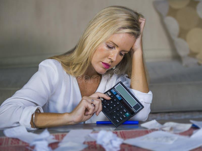 Zmartwiona i desperacka blond kobieta kalkuluje domowego pieniądze exp obraz royalty free
