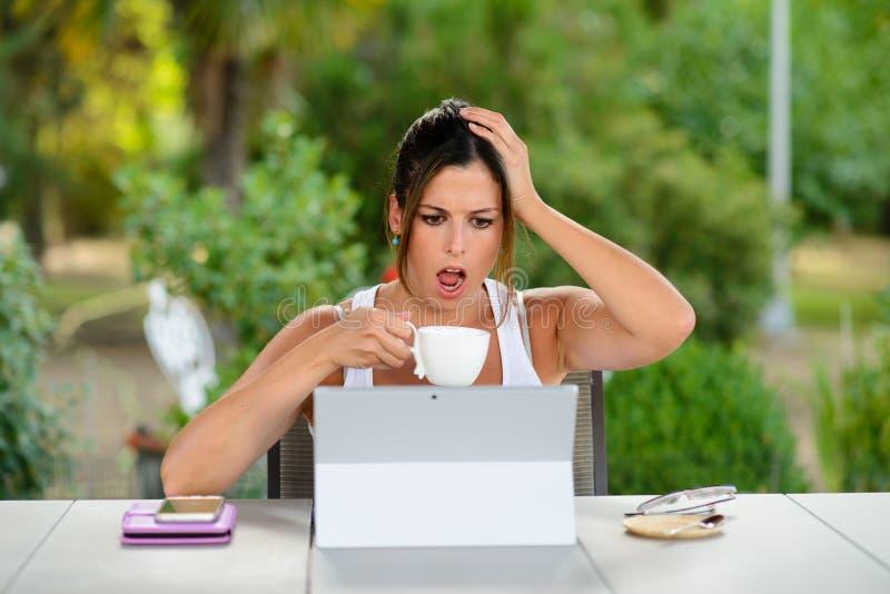 Zmartwiona kobieta pracuje online z laptopem outside zdjęcia stock
