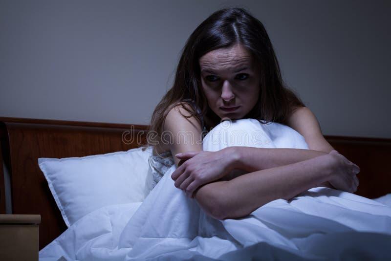 Zmartwiona kobieta w łóżku obraz royalty free
