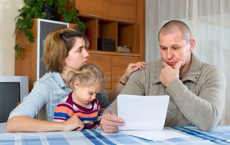 Zmartwiona rodzina z pieniężnymi dokumentami zdjęcie stock