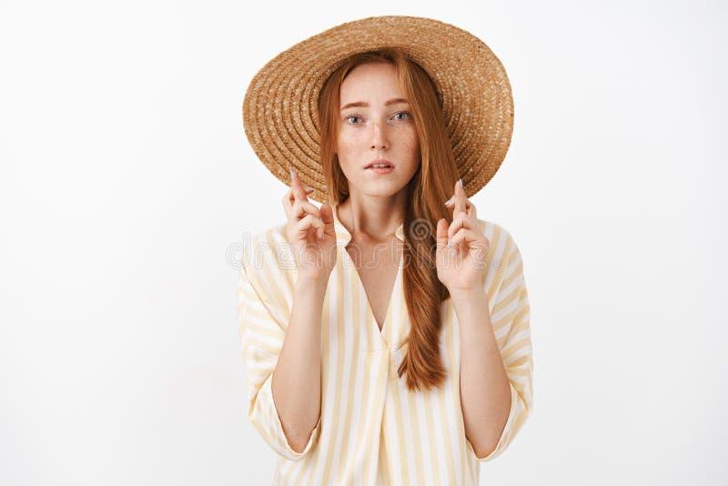 Zmartwiona skoncentrowana atrakcyjna imbirowa dziewczyna z piegami w ślicznego lata słomianym kapeluszu i pasiastym bluzki skrzyż obraz royalty free