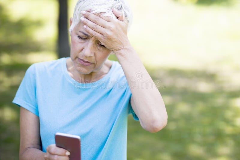 Zmartwiona starsza kobieta czyta wiadomość na telefonie komórkowym obraz stock