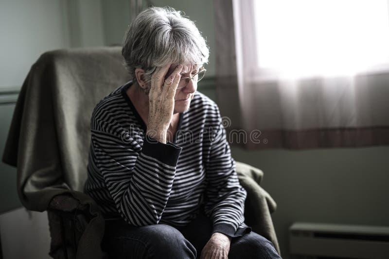Zmartwiona starsza kobieta powalać bardzo bad w domu zdjęcie stock