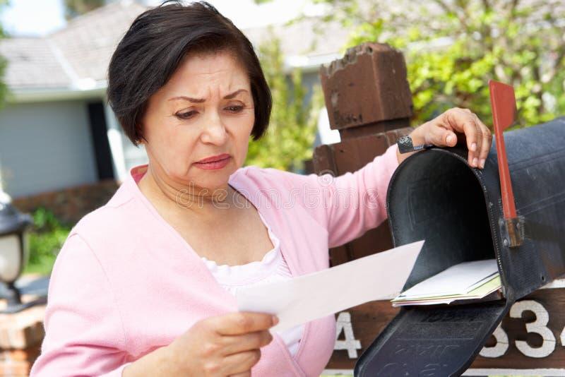 Zmartwiona Starsza Latynoska kobieta Sprawdza skrzynkę pocztowa obraz royalty free