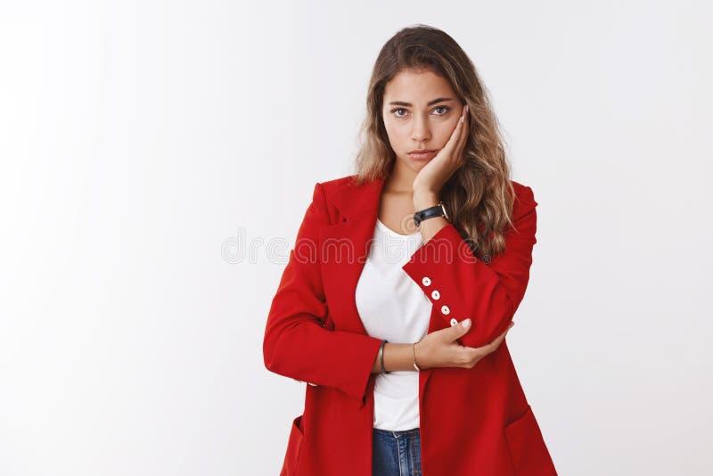 Zmartwiona zdumiona skołatana śliczna smutna millennial 25s kobieta jest ubranym czerwoną kurtkę facepalming, oparty kierowniczy  fotografia stock