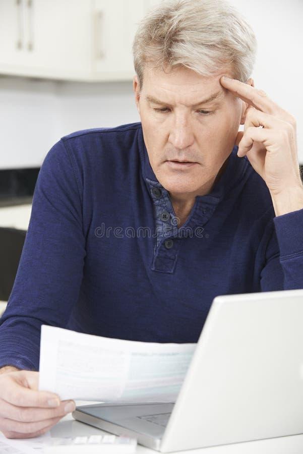 Zmartwionego Dojrzałego mężczyzna Przyglądający Przegląda finanse W Domu zdjęcia stock