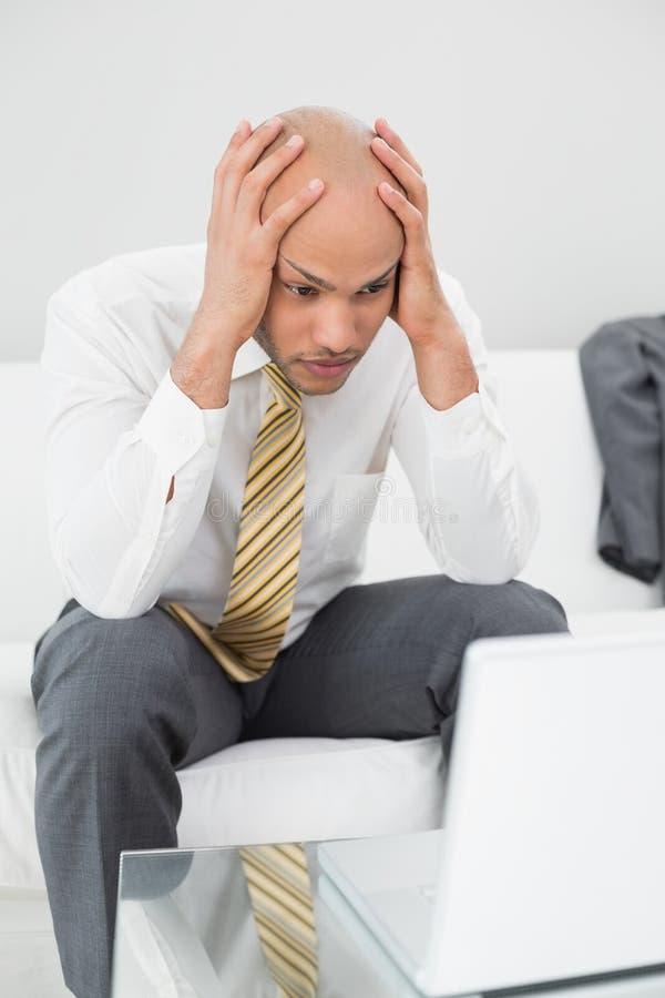 Zmartwiony biznesmen z laptopu mienia głową w rękach w domu obraz stock
