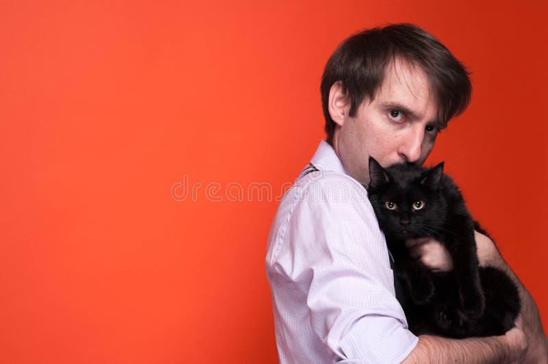 zmartwiony człowiek w różowej koszuli z tulejami trzymającymi i przytulającymi słodkiego czarnego kota i patrzącymi na kame obrazy royalty free