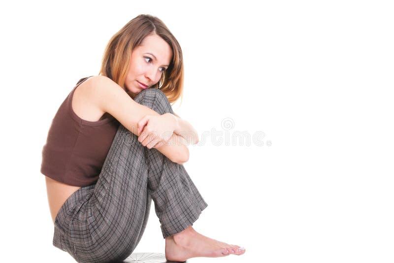 Zmartwiony i przestraszony młodej kobiety obsiadanie na krześle. Odosobniony zdjęcie royalty free