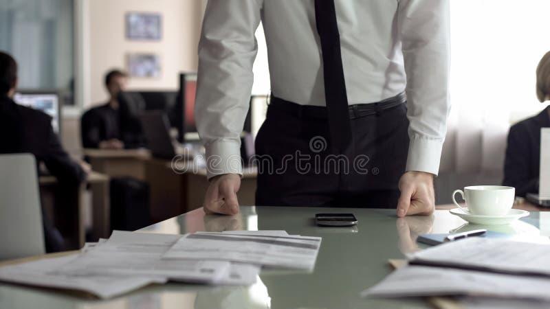 Zmartwiony kierownik opiera na stole, sfrustowanym po tym jak telefon rozmowa, problemy przy prac? zdjęcie royalty free