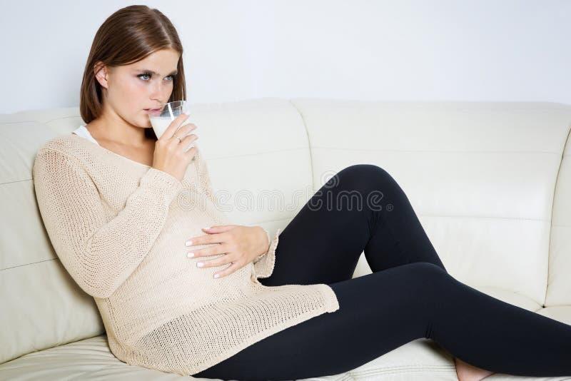 Zmartwiony kobieta w ciąży pije mleko zdjęcie stock