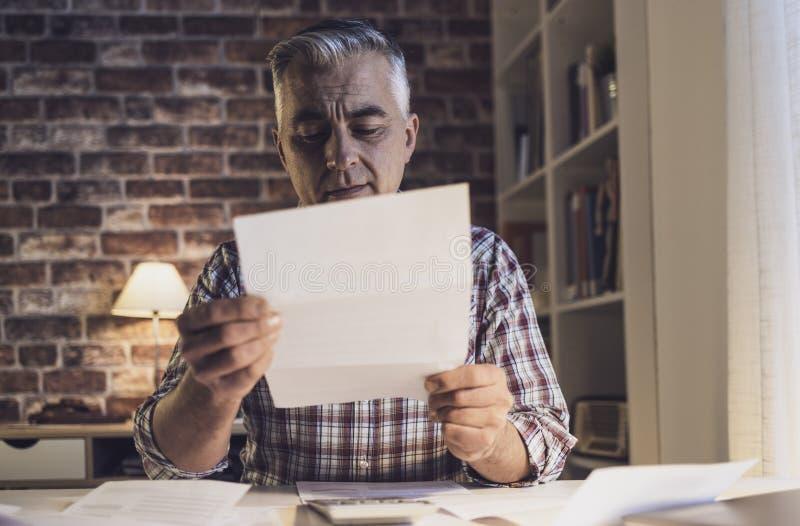 Zmartwiony mężczyzna sprawdza jego domowych rachunki w domu zdjęcia royalty free