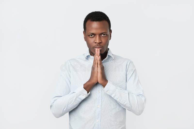 Zmartwiony młody amerykanin afrykańskiego pochodzenia mężczyzna stawiający wręcza wpólnie pyta dla pomocy przebaczenia w modlitwi fotografia stock